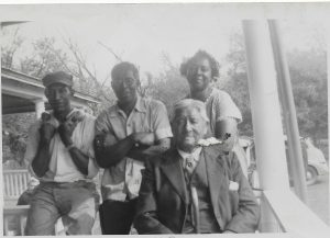 "Fig. 5: Vincent Joseph and his sister, Elizabeth Joseph Scott, were identified as ""full-blooded Montauk Indians"".  Elizabeth married Albert Scott, former slave from Virginia.  This photo shows Vincent, age 83, and unidentified male members of the Scott Chase family, with Laura Scott Chase.  Laura had married Ben Chase in 1918.  The photo is dated 1949 after the death of Albert Scott. (from the SIHS Archives)"